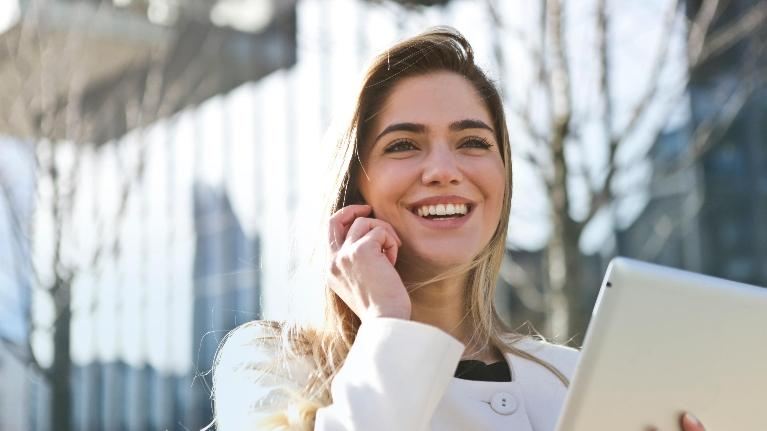 Young Woman on Cell Phone | Modern Dentures in Aurora